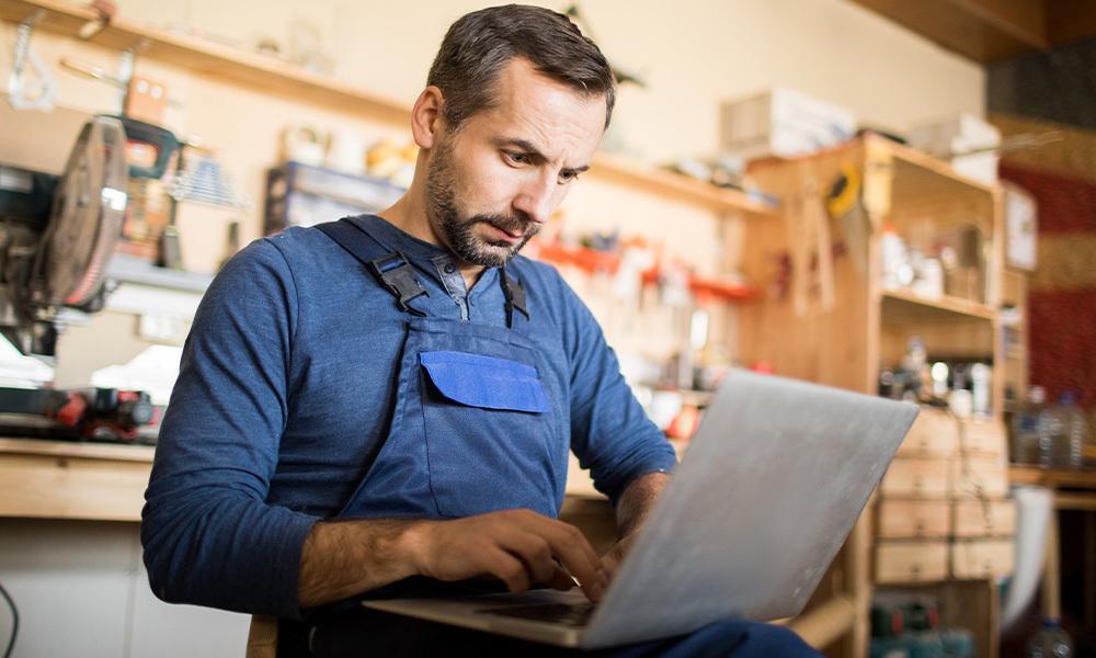 Comerciante con una laptop, de fondo se ve su pequeño negocio